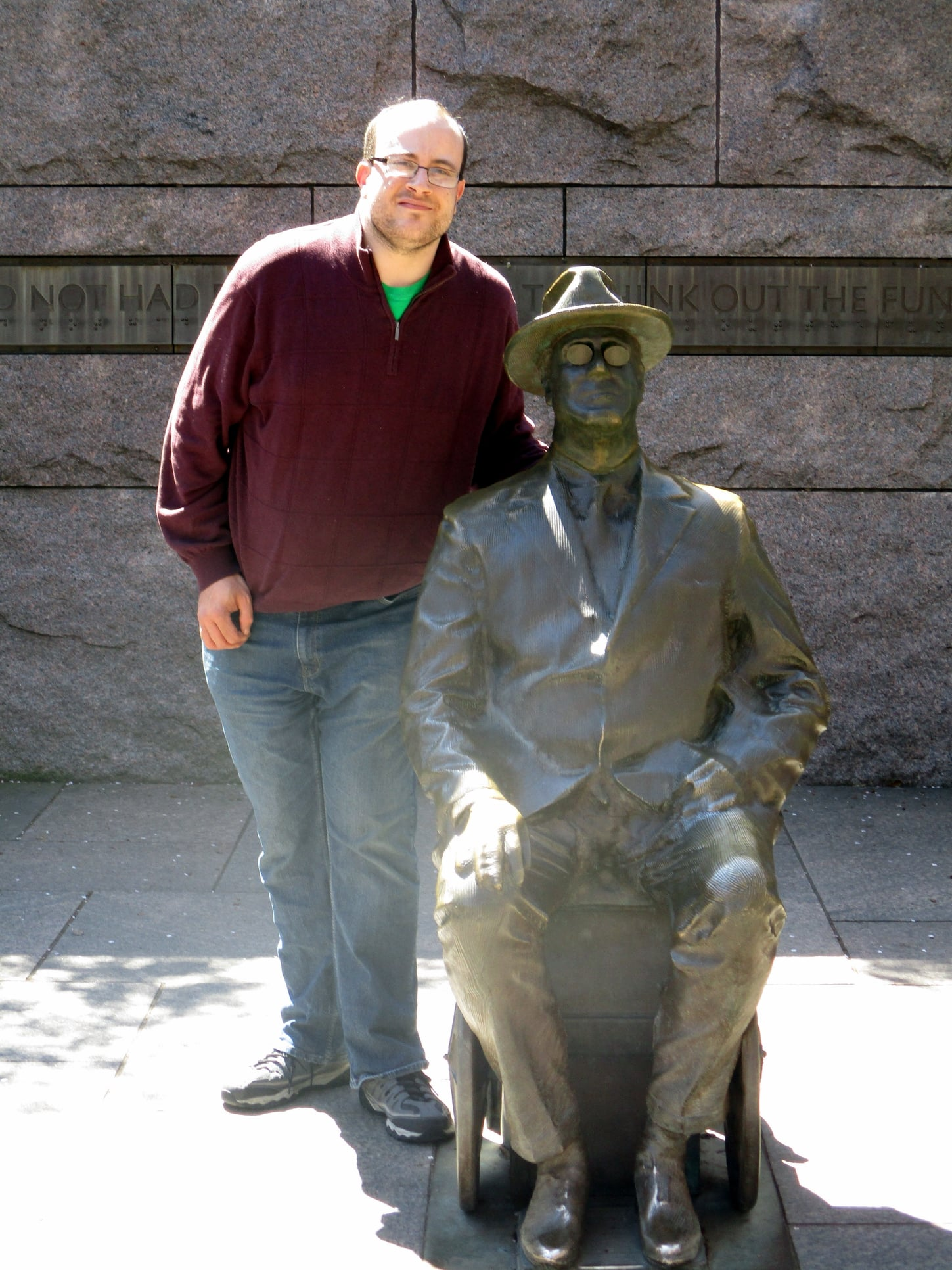 Alec Frasier standing next to FDR wheelchair statue