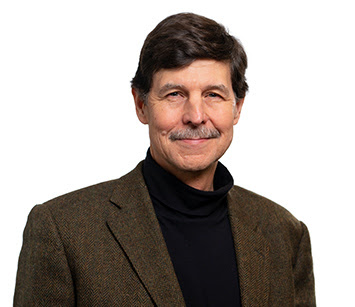 Headshot of David Woolner, Ph.D in a brown jacket and black turtle neck